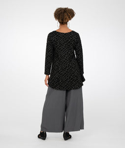 model in gray wide led pants worn with a black top with a grey geometric print, standing in front of a white background
