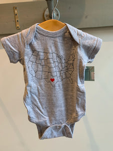 a light grey baby onesie with a drawing of  the united states with a heart in the center of texas