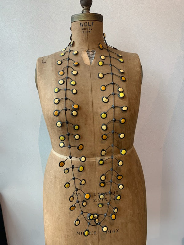 Yellow rubber necklace on an old mannequin