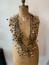 Load image into Gallery viewer, Black and yellow rubber necklace on an old mannequin