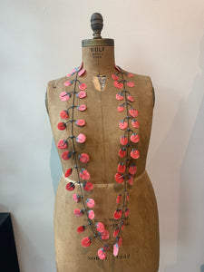 Coral/ red rubber necklace on an old mannequin