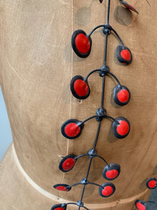 Red rubber necklace on an old mannequin, close up