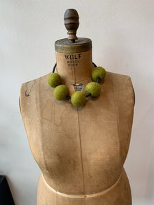 a necklace made of five green felt balls on an old mannequin