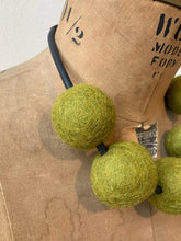 Load image into Gallery viewer, a necklace made of five green felt balls on an old mannequin
