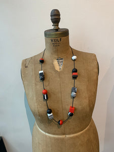 Pictured is a brown body form wearing an adjustable necklace that is fully extended to feature how long it can be worn. The necklace features a black cord with cube and sphere shaped resin beads that are spaced out and multicolored in different red, white, and black patterns. The body form is pictured in front of a white wall.