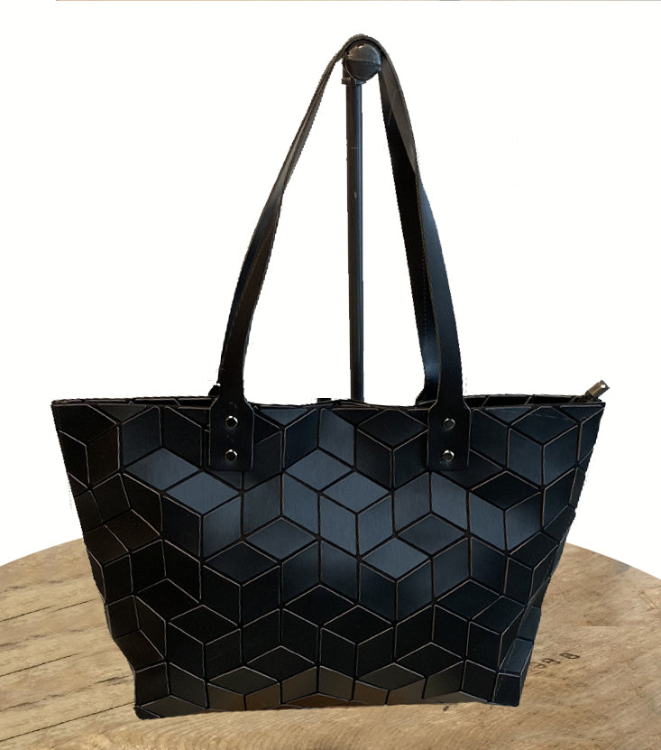 Matte black, large rectangle shaped tote bag with long shoulder straps hanging off of a hook against a white backdrop. The tote features a chevron shaped geometric pattern.