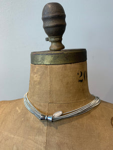 Pictured is the back of a brown body form wearing a silver necklace shown to feature the silver magnetic clasps.