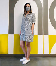 Load image into Gallery viewer, model in a black and white striped button up dress with matching mask, standing in front of a painted wall with the words 'niche'
