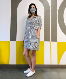 model in a black and white striped button up dress with matching mask, standing in front of a painted wall with the words 'niche'