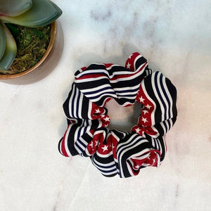black, white and red striped scrunchie with white stars in the thick red lines