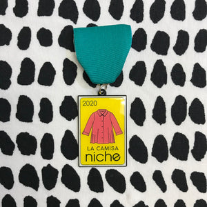 "fiesta medal with a teal ribbon on a black and white dot background. The medal is yellow with a coral color blouse and the text ""2020"" ""la camisa"" and ""niche"""