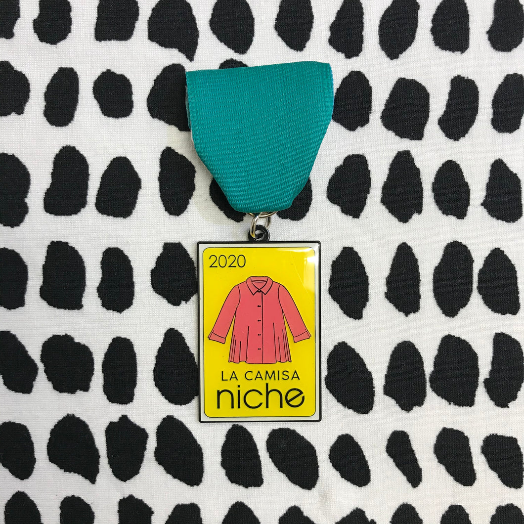 fiesta medal with a teal ribbon on a black and white dot background. The medal is yellow with a coral color blouse and the text