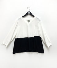 Load image into Gallery viewer, black and white color blocked pullover top with the color changing at the waist. top is white, bottom is black