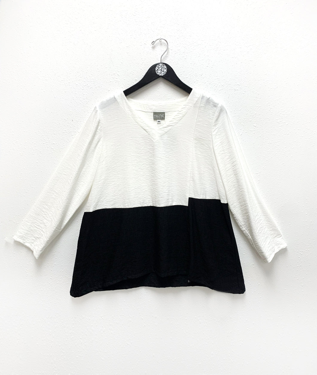 black and white color blocked pullover top with the color changing at the waist. top is white, bottom is black