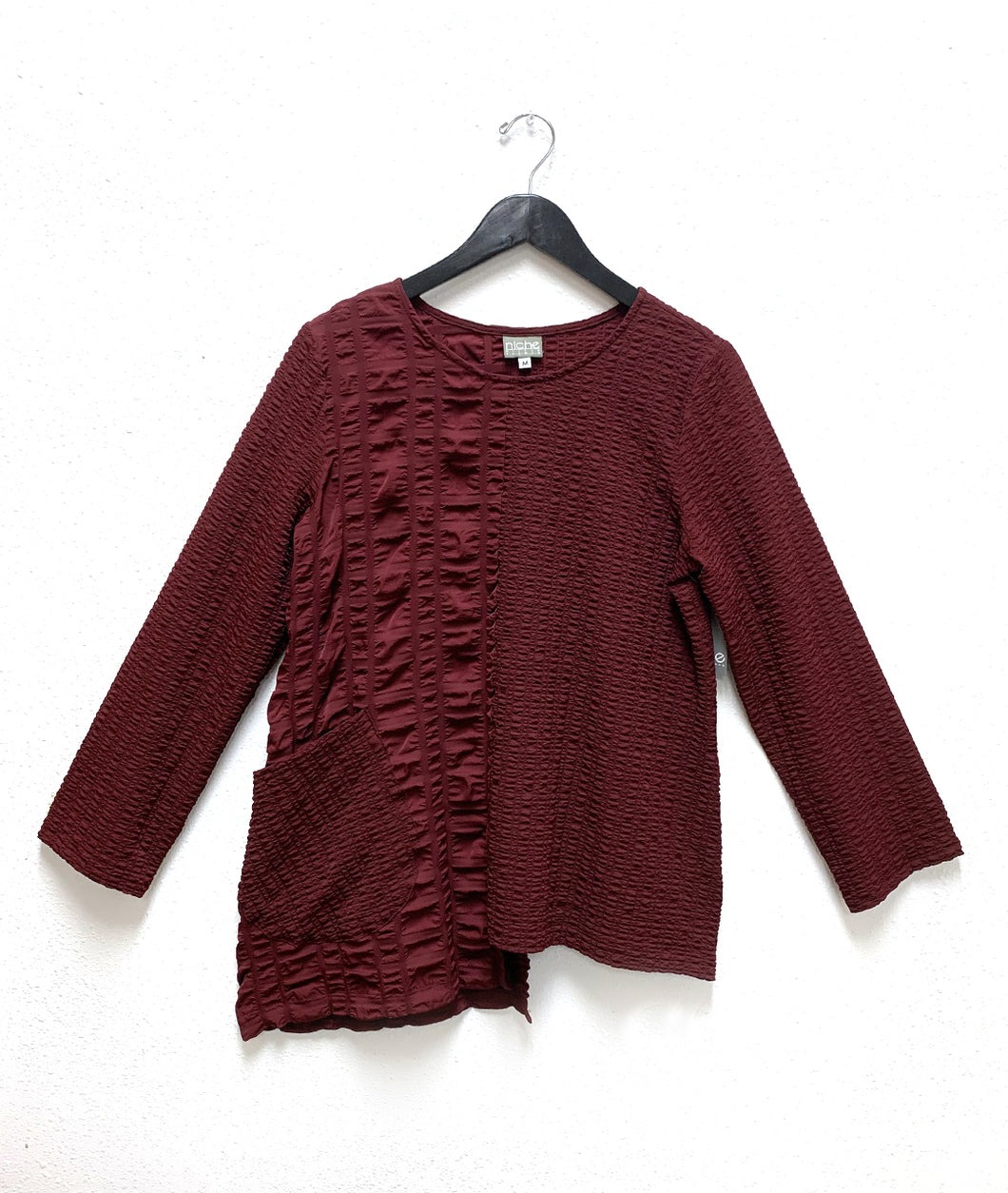 merlot color top with two different textures on either side. tunic has an uneven hem and a single square hip pocket.