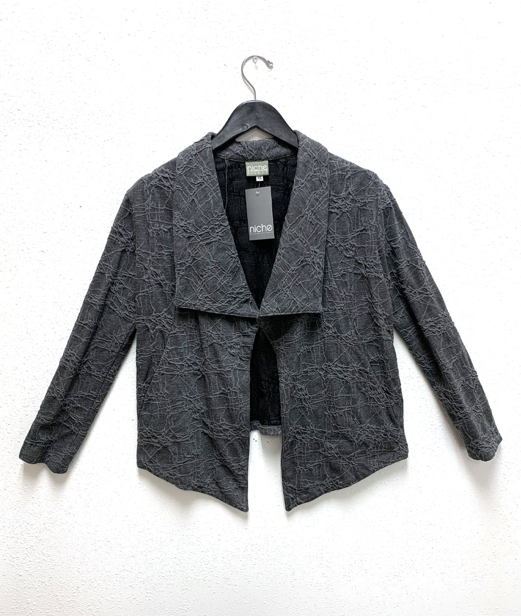 grey jacket in a web print knit. jacket has a draped large collar and long sleeves, and the body hem is lower in the front center than the rest of the body