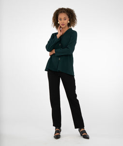 model in a dark green button up blouse with a slim, straight leg black pant, in front of a white background