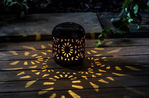 Pictured in a dark setting and on a wooden table is a solar powered lantern. The lantern features a medallion style cutout and there is light in patterns of medallions reflected onto the wooden table.