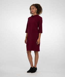 model in a burgundy dress with a shawl style collar and shaping darts at the skirt hem