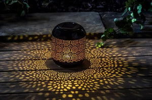 Pictured in a dark setting and on a wooden table is a solar powered lantern. The lantern features a floral style cutout and there is light in floral patterns reflected onto the wooden table.