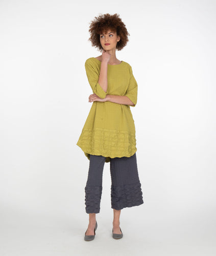 model in a lime tunic with dark gray pants in front of a white background