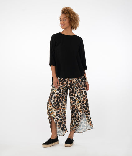 model in a solid black top with animal print pants in front of a white background