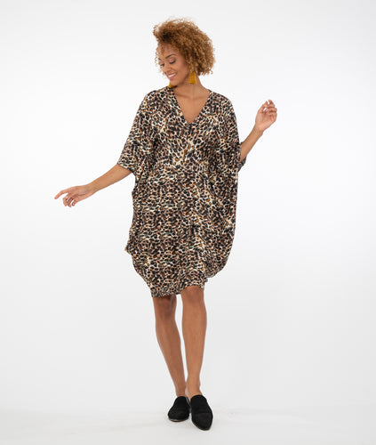model in an animal print kaftan style dress in front of a white background
