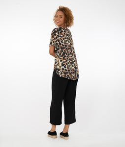 model in an animal print top with black pants in front of a white background