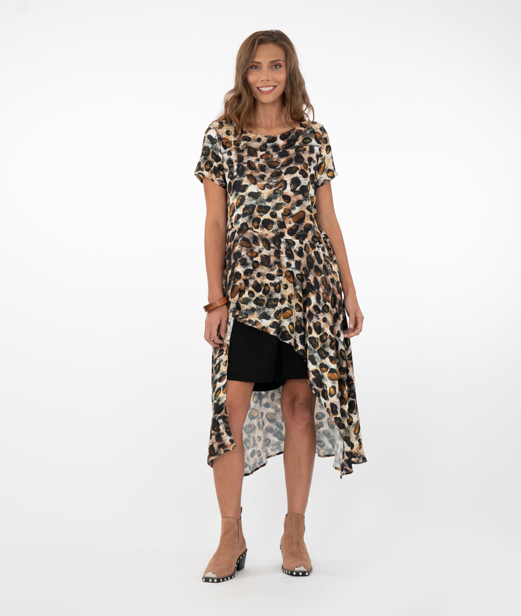 model in an animal print button up with black shorts in front of a white background