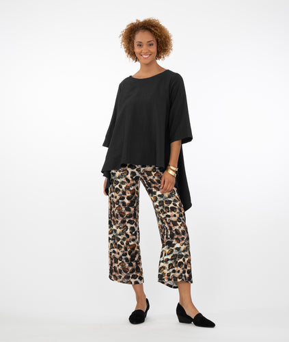 model wearing a black top with animal print pants in front of a white background