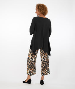 model in animal print pants with a black top in front of a white background
