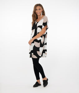 brunette model in a tan/black/white tunic with black leggings in front of a white background