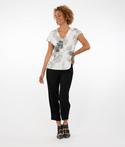 model in a slim cropped black pant with a white v-neck top with a center front seam and cap sleeves, in a multi grey tone cloud print