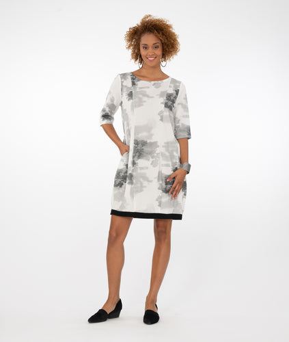 model in an above the knee length shift dress. Dress has elbow length sleeves, a contrasting black band at the hem, and princess seams down the front and back. Dress is white with a multi grey toned cloud print.