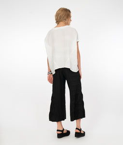 a blonde model wearing black pants and a white top in front of a white background
