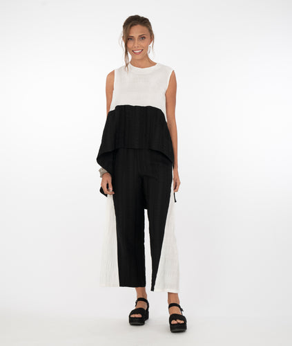 a brunette model wearing a balck and white top with black and white pants in front of a white background