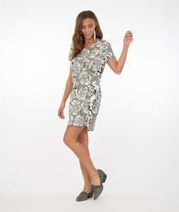brunette model in a gray and white floral dress with two ties on the front. standing in front of a white background.