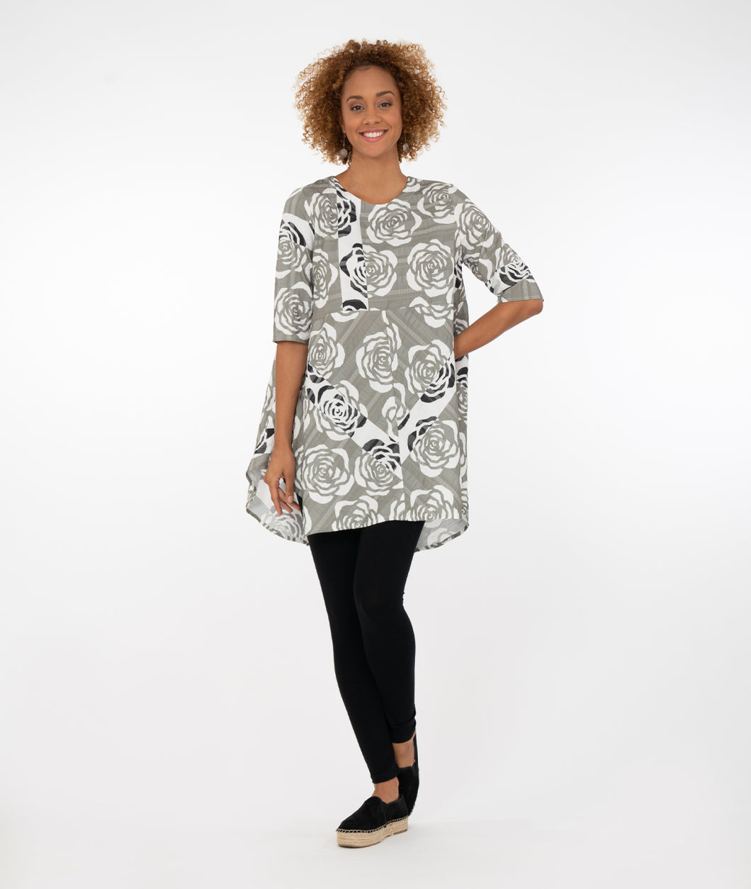 model wearing a gray and white floral design top with black leggings in front of a white background