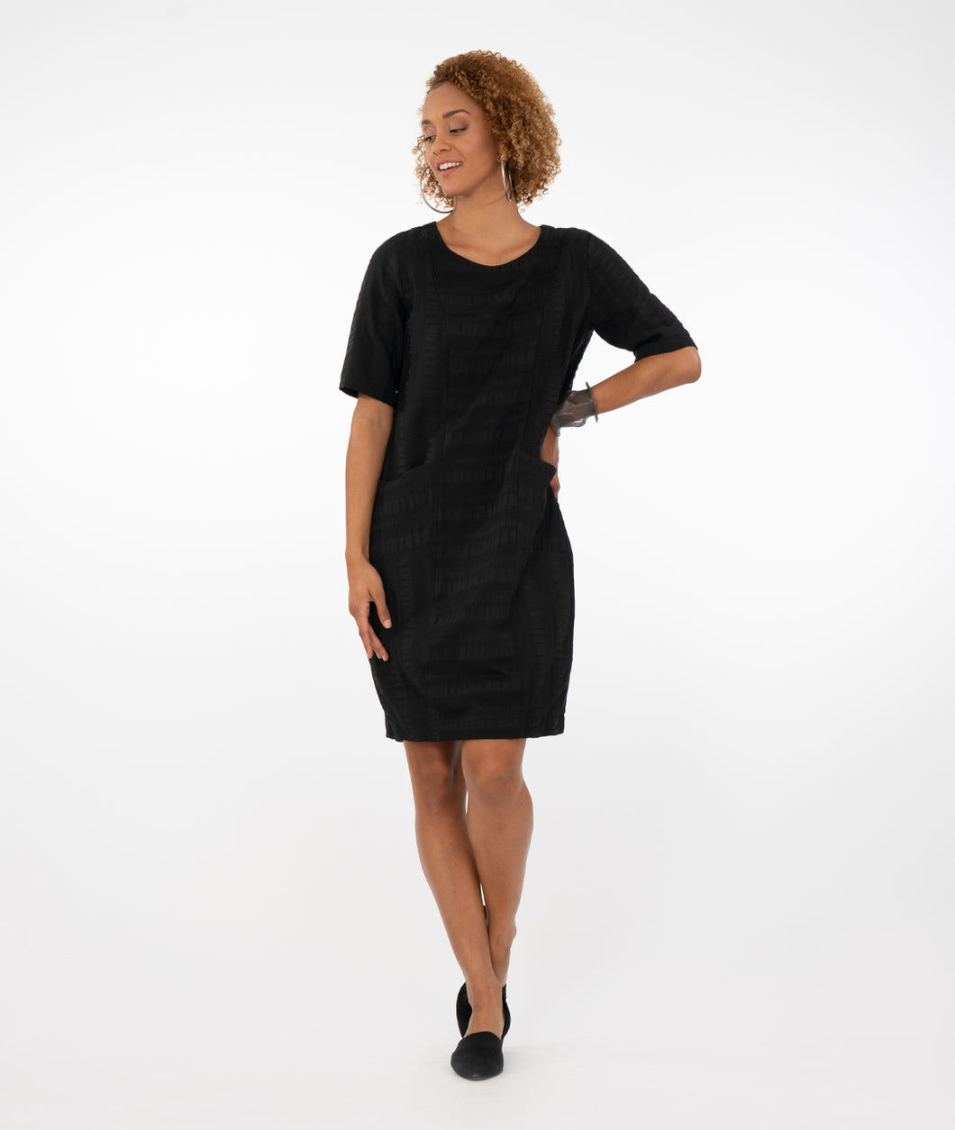 model in a black dress in front of a white background