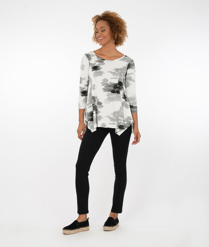 model wearing a black and white floral  top with black leggings in front of a white background