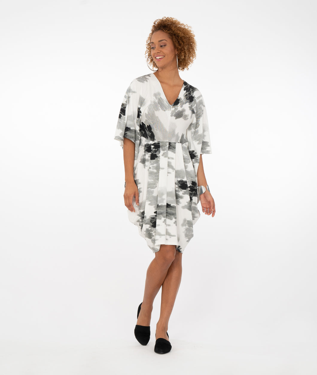 model wearing a black and white floral dress in front of a white background