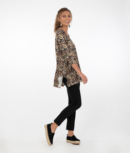 Brunette model in an animal print 3/4 sleeve top with black pants in front of a white background