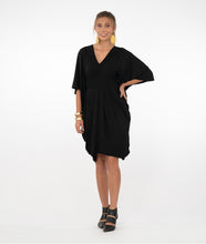 Load image into Gallery viewer, Brunette model in a black kaftan style dress in front of a white background