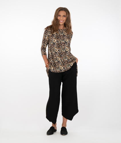 model in an animal print pull over top with black pants, in front of a white back ground