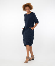 Load image into Gallery viewer, model in a navy blue dress with tuck detailing at the bottom, standing in front of a white background