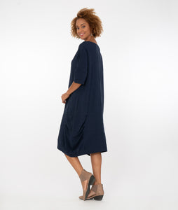 model in a navy blue dress with tuck detailing at the bottom, standing in front of a white background