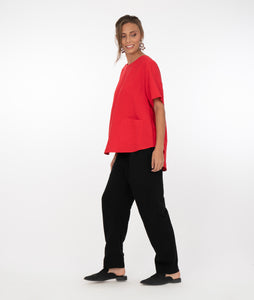 brunette model in a red top with black pants in front of a white background