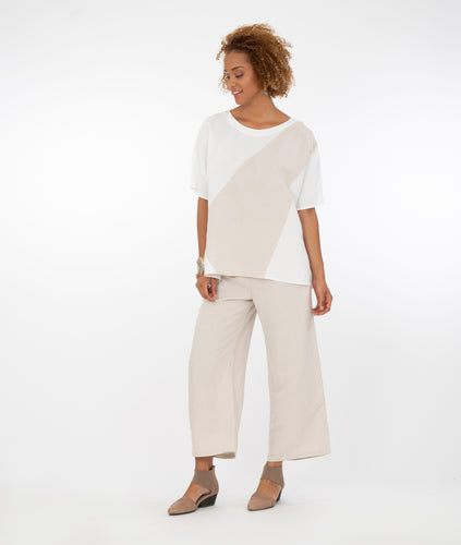 model in a white pullover tshirt style top with a contrasting color block across the body in a khaki color, with wide leg khaki color pants