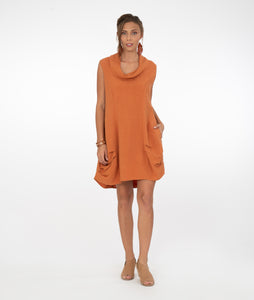 model in a sleeveless burnt orange tunic with a cowl neck and pleating along the bottom on the princess seams at the hips