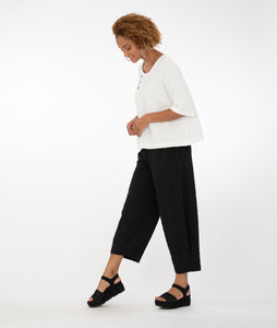 model wearing a white top with buttons at the neckline with black pants in front of a white background